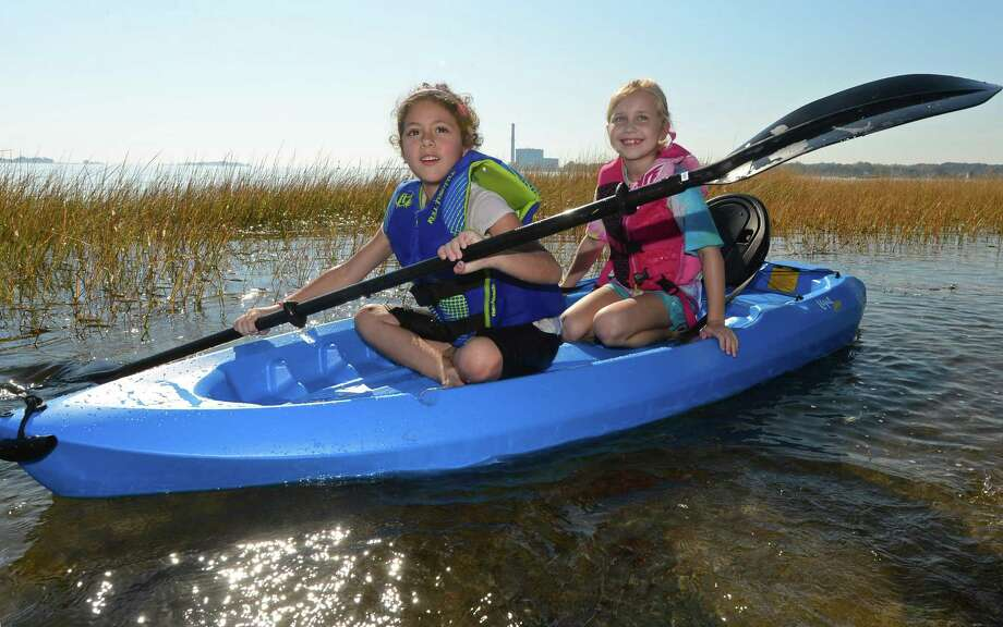 Juliana McCurdy, 6, and Lexie Ward, 8, paddle their kayak close to the shoreline at Calf Pasture Beach in Norwalk, Conn., as they enjoy the unseasonably warm weather Tuesday, October 18, 2016. Photo: Erik Trautmann / Hearst Connecticut Media / Norwalk Hour