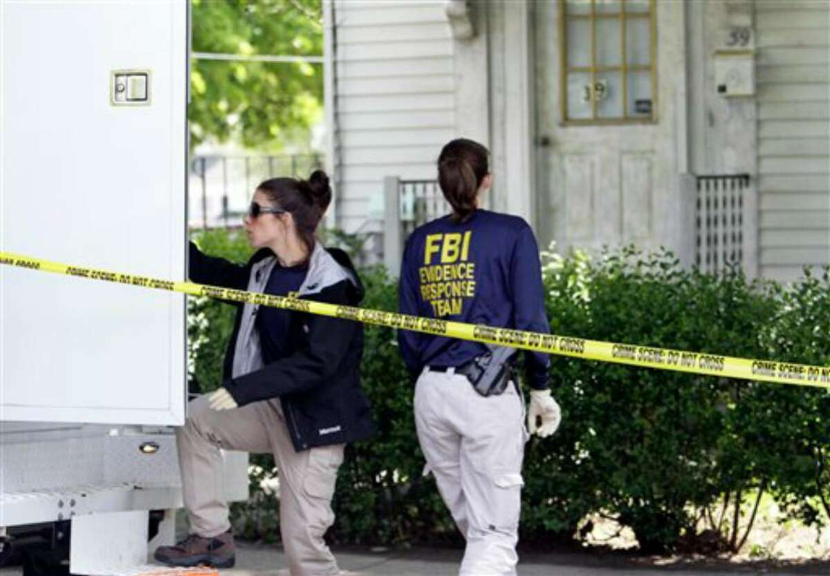 FBI investigators move between a van and a home at 39 Waverley Avenue, in Watertown, Mass., Thursday, May 13, 2010. Federal agents arrested two people and are searching locations in Massachusetts and New York on Thursday in connection with the failed Times Square car bomb, federal authorities said. (AP Photo/Steven Senne)