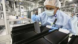 A Mission Solar Energy employee checks solar wafers in 2014. The San Antonio-based company shed hundreds of jobs in late-2016 as it struggled to compete with foreign competition. Two other U.S. solar manufacturers successfully argued to the International Trade Commission that they suffered injury due to foreign competition.