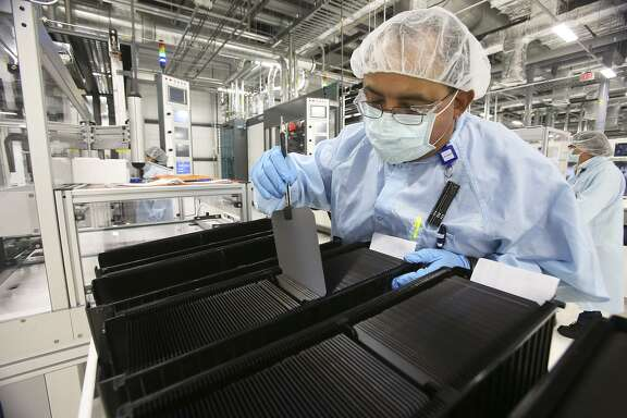 A Mission Solar Energy employee organizes solar wafers at the company's San Antonio manufacturing facility in 2014. In the face of stiff competition from Asia the company shed more than 250 jobs at the late-2016 and early-2017; it is now hiring 50 people to meet rising demand.