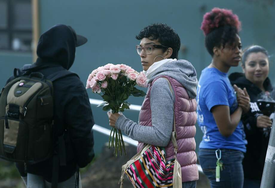 A woman who declined to give her name holds flowers before classes resume at June Jordan School for Equity in San Francisco, Calif. on Wednesday, Oct. 19, 2016, following a shooting that wounded four students after school Tuesday. Photo: Paul Chinn, The Chronicle
