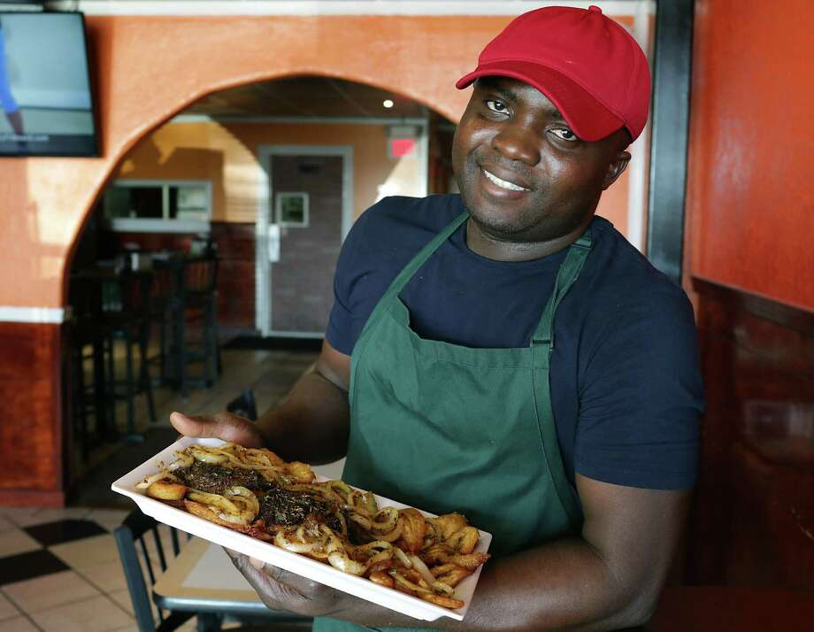 Stephen Ekwunife, owner and executive chef of Kobams African Restaurant, makes an especially good grilled whole tilapia with onions and fried plantains. Photo: Bob Owen /San Antonio Express-News / ©2016 San Antonio Express-News