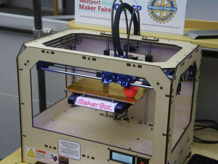 """A 3-D printer in the Westport Library's Maker Space """"prints"""" an apple. Photo: Paul Schott / Paul Schott / Westport News"""