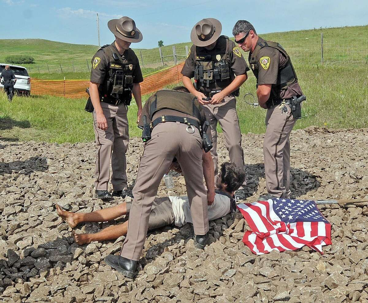 Law enforcement officers stand over a protester at the site of where a roadway was being built for construction of the Dakota Access Pipeline on Thursday, Aug. 11, 2016, in rural Morton County, N.D. The pipeline would start in North Dakota and pass through South Dakota and Iowa before ending in Illinois. (Tom Stromme/The Bismarck Tribune via AP)