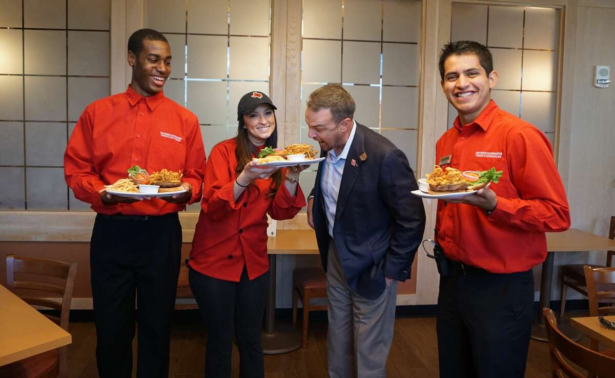 University of Houston coach Tom Herman prepares to chow down on his burger at Barron's, the student-run restaurant at Hilton College on the University of Houston campus, with (from left) Dezmon Tinsley, Loyanne Alvarado and Humberto Sanchez.