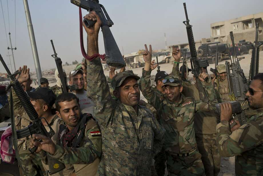Iraqi army soldiers raise their weapons in celebration of victory on the outskirts of the town of Qayyarah. Photo: Marko Drobnjakovic, Associated Press