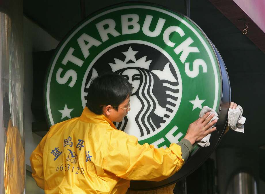 (FILES) This file photo taken on January 2, 2006 shows window cleaners as they wipe clean a Starbucks sign in front of a franchise of the US coffee chain in Beijing. US coffeehouse chain Starbucks on October 19, 2016 announced a five-year goal of doubling the number of its stores in China, which could soon become its largest market.Starbucks has seen rapid expansion in China, where it opened its first cafe 17 years ago. In 2011, the company had only 400 outlets but today has almost six times as many at 2,300.  / AFP PHOTO / FREDERIC J. BROWNFREDERIC J. BROWN/AFP/Getty Images Photo: FREDERIC J. BROWN, AFP/Getty Images