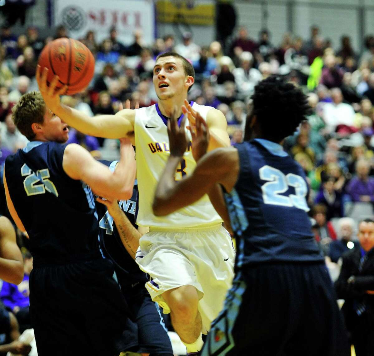 Joe Cremo of the UAlbany drives to the basket through two Maine players during their game on Sunday, Feb. 14, 2016, in Albany, N.Y. (Paul Buckowski / Times Union)