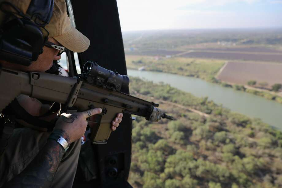 A U.S. Customs and Border Protection agent scans the U.S.-Mexico border from a helicopter patrol on October 18, 2016 near McAllen, Texas. U.S. Air and Marine Operations agents fly over border areas, coordinating with Border Patrol agents on the ground to stop undocumented immigrants and drug smugglers from entering the U.S. Immigration and border security have become major issues in the American Presidential campaign.  (Photo by John Moore/Getty Images) Photo: John Moore/Getty Images