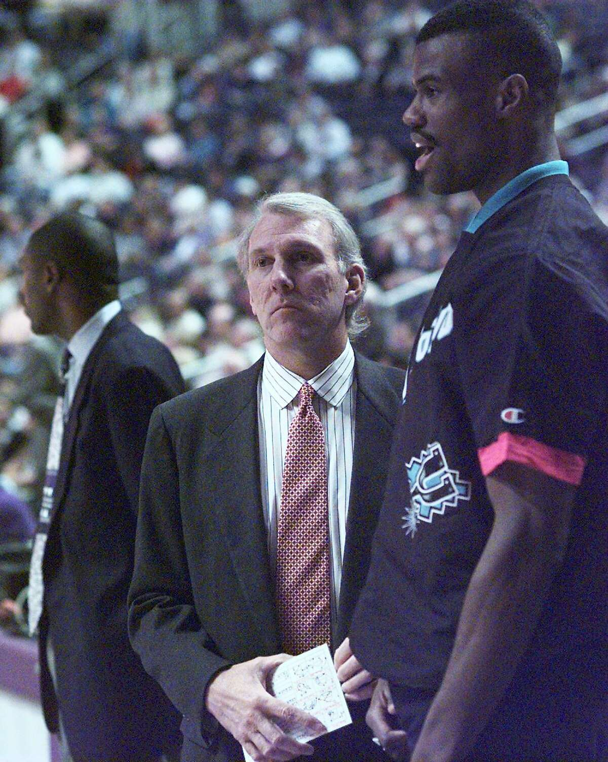 New Coach Gregg Popovich and David Robinson confer just before the start of the game in Phoenix against the Suns on Dec. 10, 1996, which the Spurs lost.