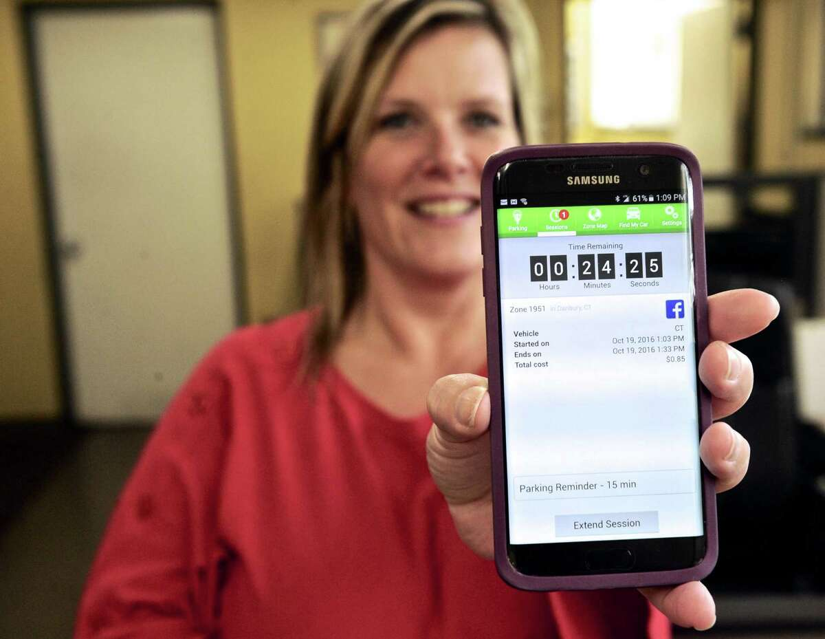 The Danbury Parking Authority has announced mobile payments for downtown parking through the ParkMobil App for Android and iPhone. Wednesday, October 19, 2016, in Danbury, Conn.DPA Administrative Assistant Tricia Archiere holds a phone with the parking app showing the time remaining.