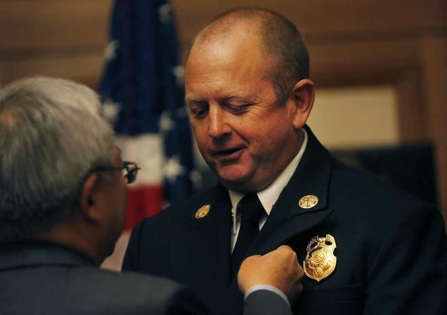 Mayor Ed Lee pins a badge onto the Assistant Deputy Fire Chief of Division 2 Robert Postel as Lee honors the first responders and a civilian who rescued 30 people from the bay when their boat capsized a few weeks ago in City Hall Oct. 19, 2016 in San Francisco, Calif. Photo: Leah Millis, The Chronicle