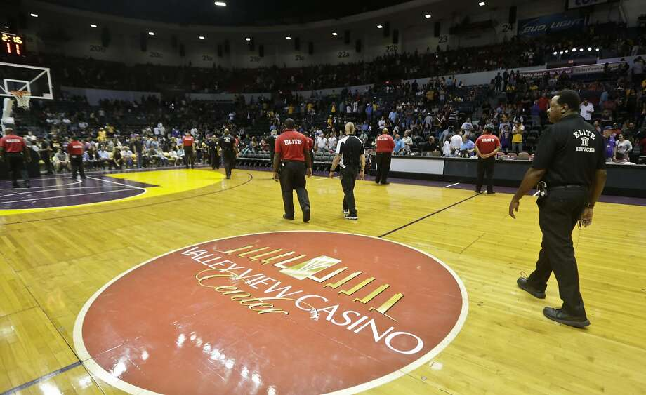 Security guards line the side of the basketball court at the Valley View Casino Center after NBA officials determined the court was too dangerous to continue play of the NBA preseason basketball game between the Los Angeles Lakers and Golden State Warriors in the third quarter Saturday, Oct. 17, 2015, in San Diego. The court had become slippery from moisture on the court caused by the ice from the hockey arena underneath the basketball floor.  (AP Photo/Lenny Ignelzi) Photo: Lenny Ignelzi, Associated Press