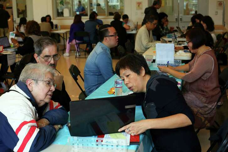 An enrollment agent helps clients last year in San Francisco. Officials predict 13.8 million will sign up for ACA coverage during the next enrollment period.