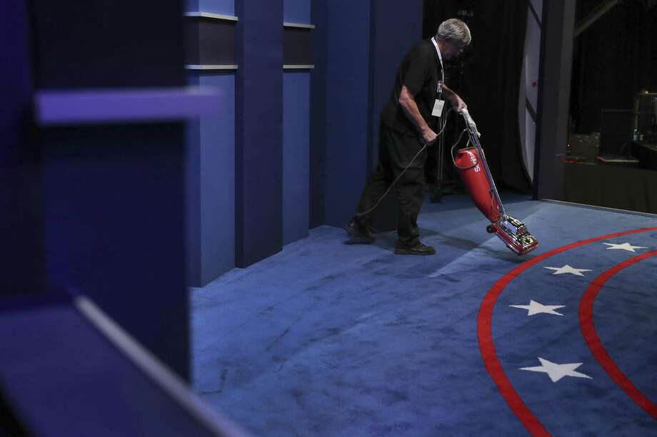 A stage hand vacuums the carpet before the third and final debate between Democratic presidential nominee Hillary Clinton Republican presidential nominee Donald Trump at UNLV in Las Vegas, Wednesday, Oct. 19, 2016. (Joe Raedle/Pool via AP) Photo: Joe Raedle, POOL / Associated Press / Copyright 2016 The Associated Press. All rights reserved.