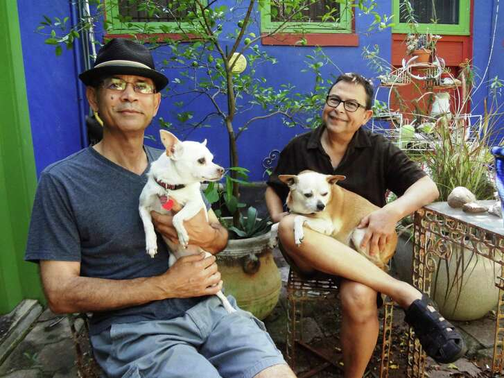 Artists Angel Rodriguez-Díaz (with 15-year-old chihuahua Xochitl) and Rolando Briseño (with 8-year-old chihuahua/pug mix Chacho) sit in the garden of their San Antonio home.