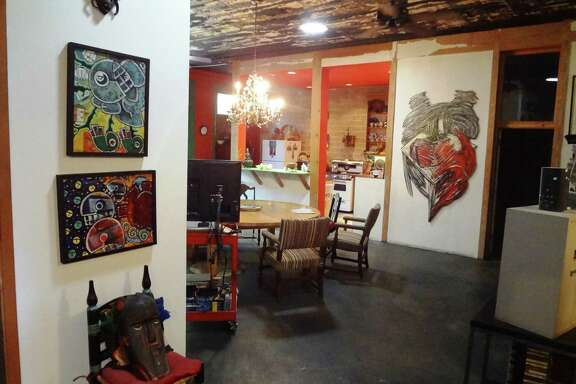 The main living area, with a large painting by Rolando Briseño on the far wall (right), was once a large freezer for a venison processing operation.
