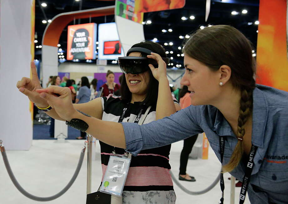 Lingzi Yang demos a pair of Microsoft HoloLens with guidance from Marjolijn Beckers in the Avanade booth during the Grace Hopper Celebration of Women in Computing conference at the George R. Brown Convention Center Oct. 19, 2016, in Houston. Photo: James Nielsen, Houston Chronicle / © 2016  Houston Chronicle