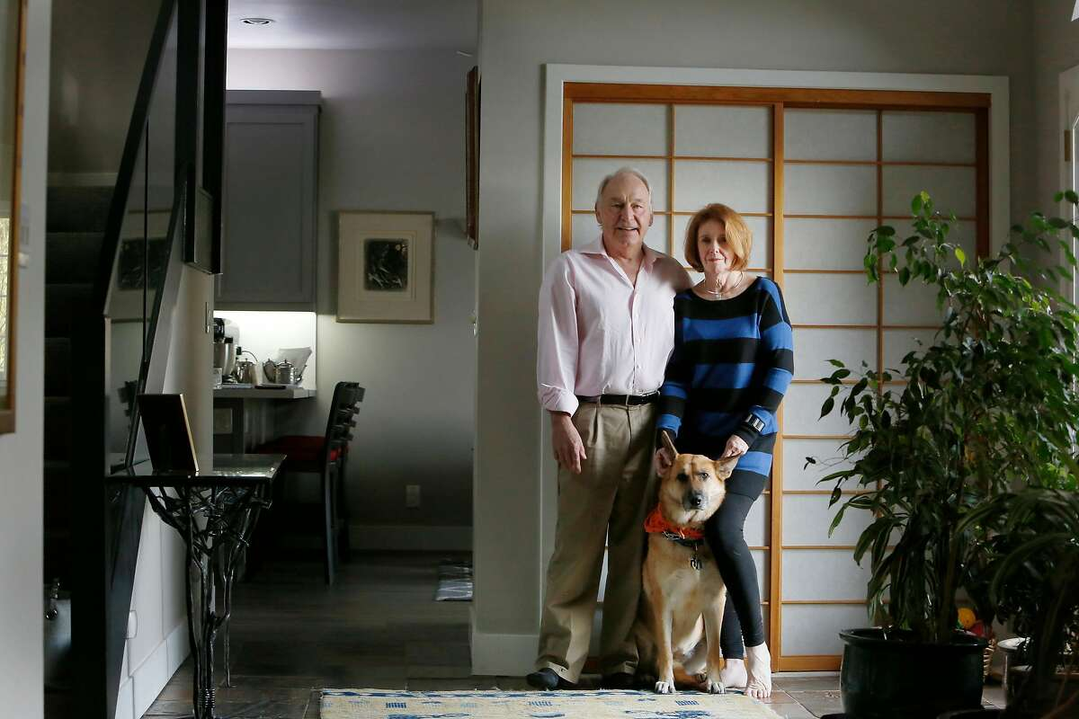 Barry Pilger (left) and Catherine Moss (right) stand for a portrait with their dog Freia (center) at their home on Thursday in Oakland. Their earlier home was burned in the Oakland Hills Firestorm in 1991.