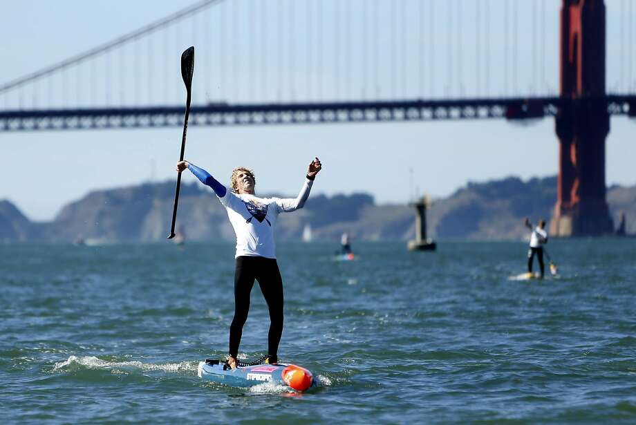 Connor Baxter celebrates his victory after negotiating the Ocean Beach surf and Golden Gate currents to reach the St. Francis Yacht Club in 1 hour, 11 minutes and 32 seconds. Photo: Scott Strazzante, The Chronicle