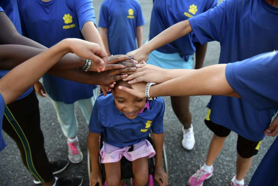 Fifth-grader Kira Wall participates in a team huddle before she competes with the cross country team at Menands School on Wednesday, Oct. 19, 2016 in Menands, N.Y. Wall was born a conjoined twin and when she was separated from her sister at birth her spinal cord was damaged. She's been in a wheelchair all her life. (Lori Van Buren / Times Union) Photo: Lori Van Buren / 20038441A