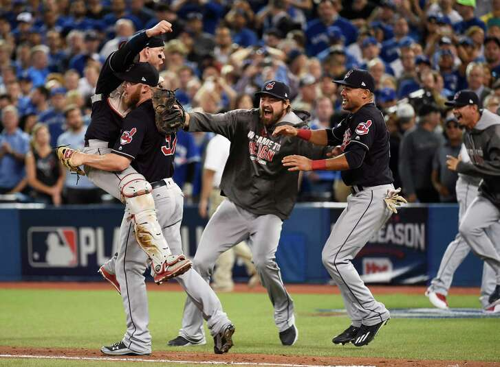 Cleveland Indians relief pitcher Cody Allen (37), cather Roberto Perez (55) and teammates Andrew Miller and Coco Crisp celebrate the team's 301 victory over the Toronto Blue Jays during Game 5 of the baseball American League Championship Series, in Toronto on Wednesday, Oct. 19, 2016. (Nathan Denette/The Canadian Press via AP)