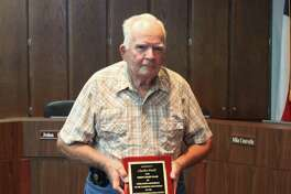 Shepherd ISD School Board Member Charles Dodd displays a plaque given to him by the school district commemorating his 38 years of service. The plaque was presented at his retirement party on Oct. 17 at the Shepherd ISD administration building.