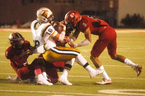 Plainview's Jace De La Garza, right, and Dice Griego, left, and teammate Brodrick Jackson, hidden, combine to bring down an Amarillo High runner last week. The Bulldogs face another important district game Thursday night when they take on Caprock.