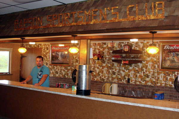 Raymond Peyerk stands behind the historic bar at Rapson Sportsman's Club.