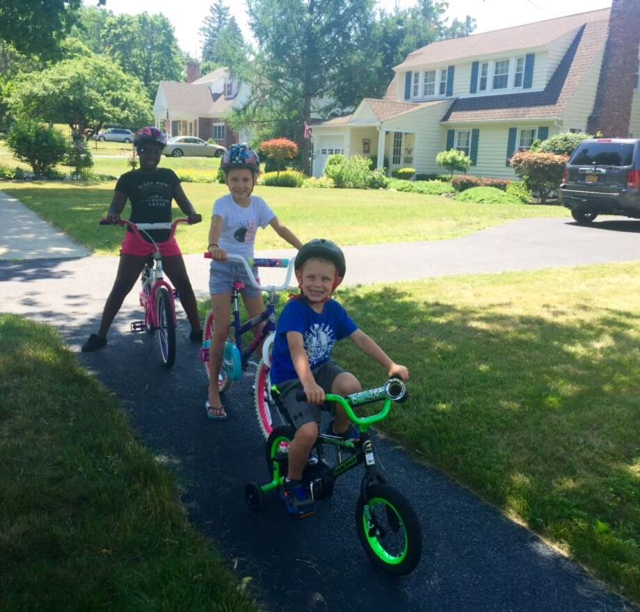 """The Casullos of East Greenbush participated in the Fresh Air Fund?s Friendly Towns Program in July and were among the winners of its 2016 photo contest. Photos capture the experiences volunteer host families shared with Fresh Air children this summer. Their photo was selected as winner in the """"biking"""" category, and features Fresh Air child, 10-year-old Tamara riding a bike in the Albany area with host siblings Brooke and Dominick. For more information, see www.freshair.org."""