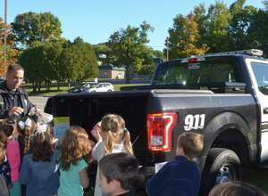 "The Northville Elementary School children bring their donations for the New Milford Food Bank to Officer Guy Scarcella during a recent ""Kick-off Kindness"" program, an initiative focusing on kind acts throughout the school."