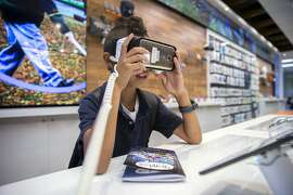Mikio Sugai, age 9, demos the virtual reality device at the new AT&T flagship retail store, Wednesday, Oct. 19, 2016 in San Francisco, Calif.