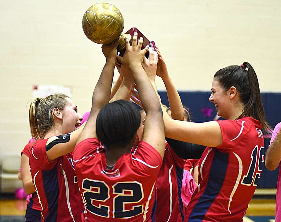 McMahon players, including outside hitters Taylor Morton, left, and Meredith Pellegrino, right, celebrate with the trophy that is awarded to the winner of the annual rivalry game against Norwalk on Wednesday night at Kehoe-King Gym in Norwalk. Photo: John Nash / Hearst Connecticut Media / Norwalk Hour