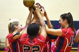 McMahon players, including outside hitters Taylor Morton, left, and Meredith Pellegrino, right, celebrate with the trophy that is awarded to the winner of the annual rivalry game against Norwalk on Wednesday night at Kehoe-King Gym in Norwalk.