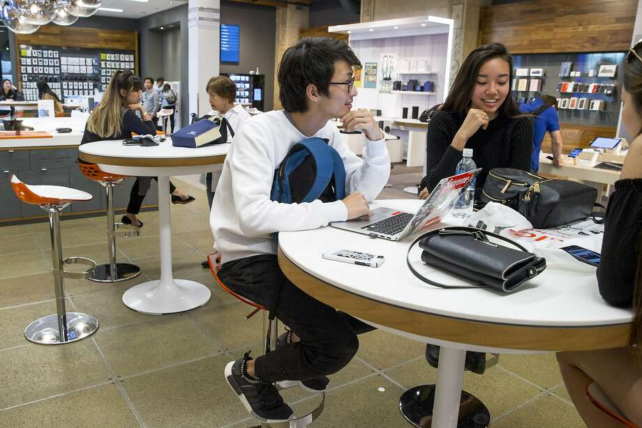 From right: Lauren Lee, Mariko Lau and Daiya Masuda (on laptop) wait to be helped at the new AT&T flagship retail store in San Francisco. Photo: Santiago Mejia, The Chronicle