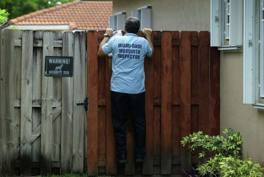 FILE - In this Tuesday, April 12, 2016, file photo, Giraldo Carratala, an inspector with the Miami Dade County mosquito control unit, peers over a fence into the backyard of a home in Miami, Fla. The government on Wednesday, Oct. 19, recommended Zika testing for all pregnant women who recently spent time anywhere in Florida's Miami-Dade County. (AP Photo/Lynne Sladky, File) ORG XMIT: NY120 Photo: Lynne Sladky / Copyright 2016 The Associated Press. All rights reserved. This material may not be published, broadcast, rewritten or redistributed without permission.