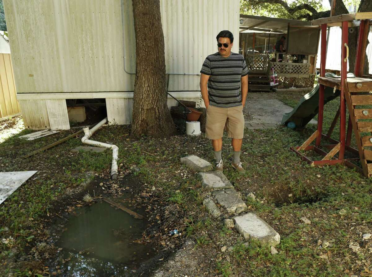 Jesus Arredondo shows one of the areas that has a problem with sewage at Oak Hollow Mobile Home Park on Oct. 19, 2016.