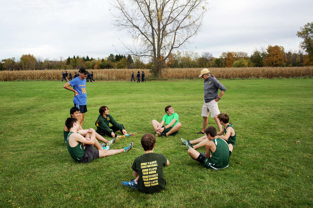 THEOPHIL SYSLO | For the Daily News Dow High School cross country coach Jed Hopfensperger, right, speaks to his runners before participating in the Saginaw Valley League cross country championship at Delta College on Wednesday.
