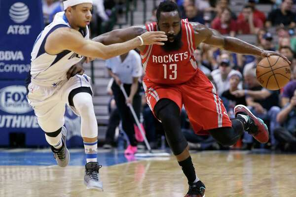 The Rockets' James Harden fends off the Mavericks' Seth Curry during the first half Wednesday night.