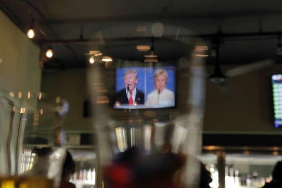 Donald Trump, left, and Hillary Clinton, right, are visible on screen through a glass during a game of Debate Bingo while watching the third presidential debate at The Good Hop in Oakland, Calif., on Wednesday, October 19, 2016. Patrons marked off phrases used by the candidates to win a shot of Underberg, a German bitters.