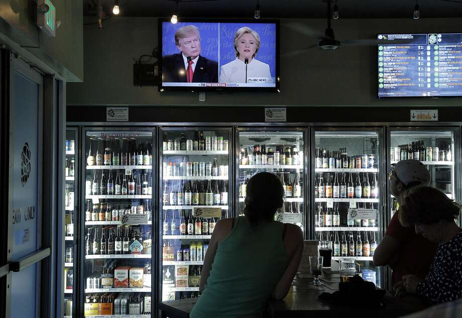 Patrons watch Donald Trump, left, and HIllary Clinton, right, during a game of Debate Bingo while watching the third presidential debate at The Good Hop in Oakland, Calif., on Wednesday, October 19, 2016. Patrons marked off phrases used by the candidates to win a shot of Underberg, a German bitters. Photo: Carlos Avila Gonzalez, The Chronicle