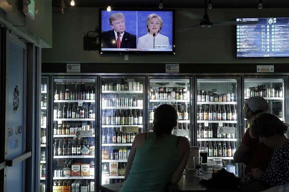 Patrons watch Donald Trump, left, and HIllary Clinton, right, during a game of Debate Bingo while watching the third presidential debate at The Good Hop in Oakland, Calif., on Wednesday, October 19, 2016. Patrons marked off phrases used by the candidates to win a shot of Underberg, a German bitters.