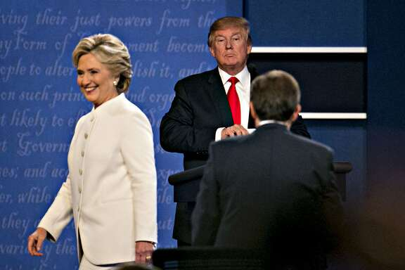 Donald Trump, 2016 Republican presidential candidate, stands as Hillary Clinton, 2016 Democratic presidential candidate, exits the stage after the third presidential debate in Las Vegas, Nevada, U.S., on Wednesday, Oct. 19, 2016. Donald Trump is trying another wild-card play in the third and final presidential debate with Hillary Clinton in perhaps his last chance to reverse his campaign's spiral and halt his Democratic rival's rising electoral strength. Photographer: Daniel Acker/Bloomberg
