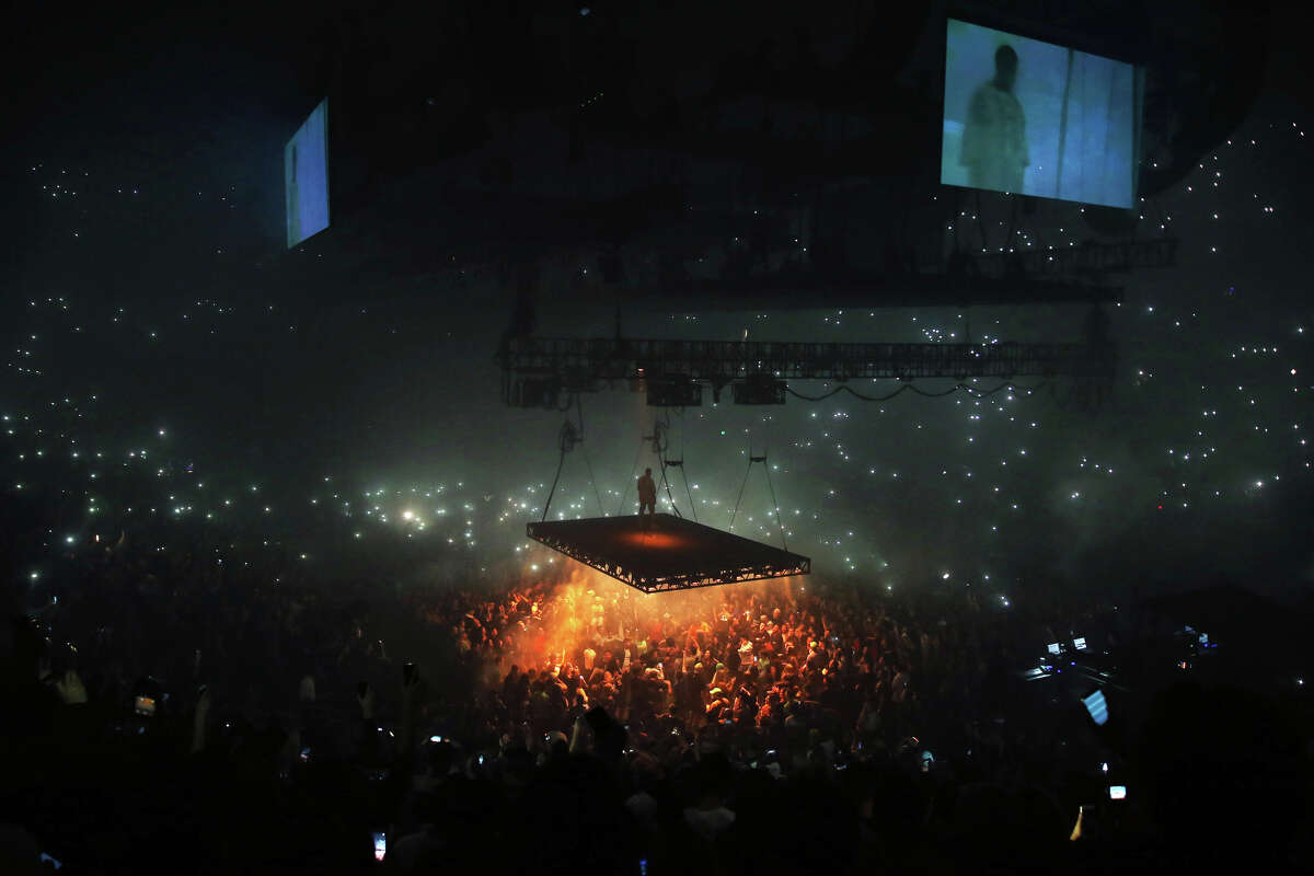 Kanye West performs on a stage that floats above the crowd during his Saint Pablo Tour at KeyArena, Wednesday, Oct. 19, 2016.