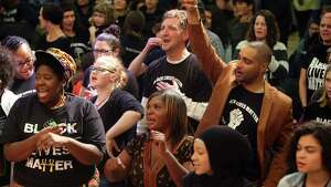 """Audience members including Garfield High teacher Jesse Hagopian (left) listen to a performance from Gabriel Teodros and Suntonio Bandanaz during a """"Black Lives Matter at School"""" rally at Washington Hall, Wednesday evening, Oct. 19, 2016.  The rally, which featured performances and discussions on race, ended a day of 2,000 Seattle teachers and many students wearing """"Black Lives Matter"""" shirts in school to call for racial equality in education."""
