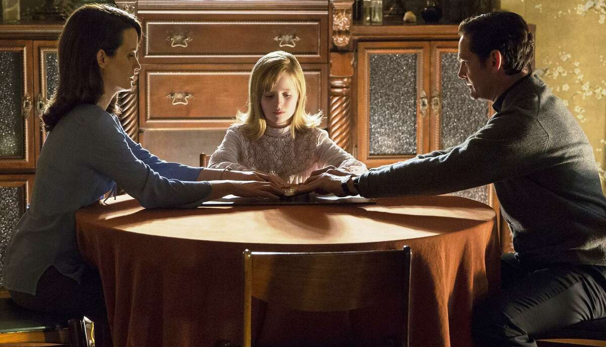 """Mom Alice (Elizabeth Reaser), freaky daughter Doris (Lulu Wilson) and their helpful priest friend (Henry Thomas) fool with a Ouija board. What could go wrong? """"Ouija: Origin of Evil"""" is a surprisingly well-made sequel that probably won't do as well as its widely panned predecessor, 2014's """"Ouija."""""""