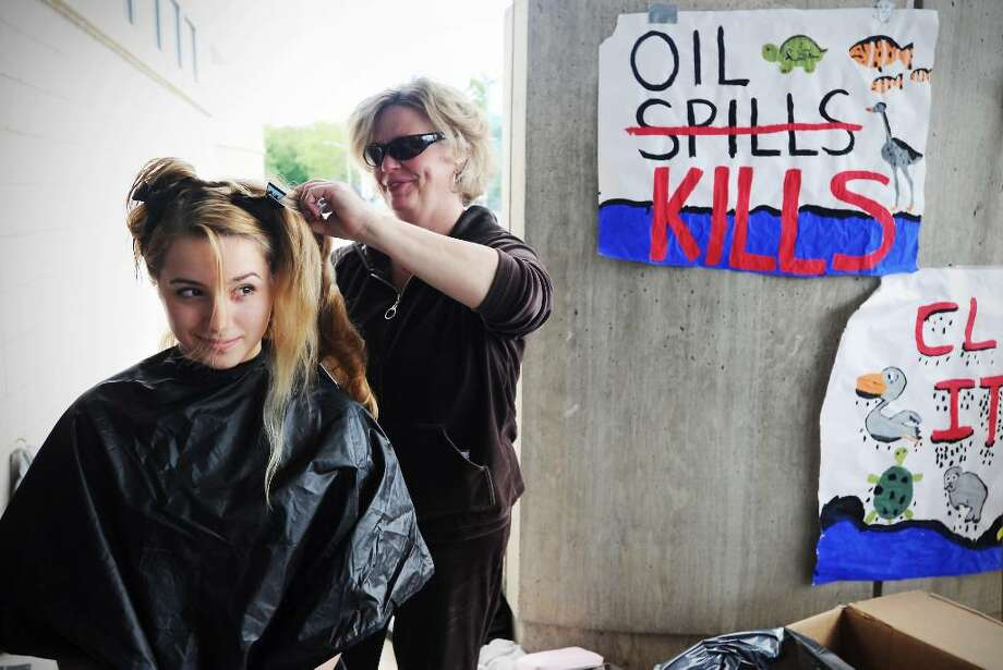 Jan White cuts Avery Welch's hair, 14, as students, friends and family at AITE get their hair cut in Stamford, Conn. on Thursday May 13, 2010 to send to an organization that is using human hair to absorb the oil spilled into the Gulf of Mexico when the BP oil rig exploded. Photo: Kathleen O'Rourke / Stamford Advocate