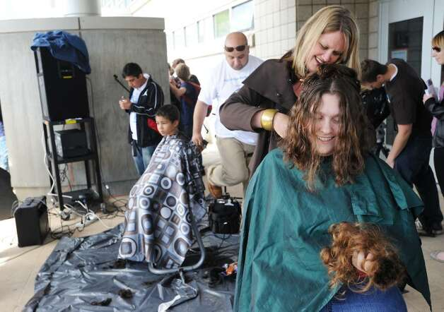 Taylor Velez, 15, holds a pile of her own hair just cut by Suellen Castros, of Briana Salon of Stamford, as students, friends and family at AITE  get their hair cut in Stamford, Conn on Thursday May 13, 2010 to send to an organization that is using human hair to absorb the oil spilled into the Gulf of Mexico when the BP oil rig exploded. Photo: Kathleen O'Rourke / Stamford Advocate