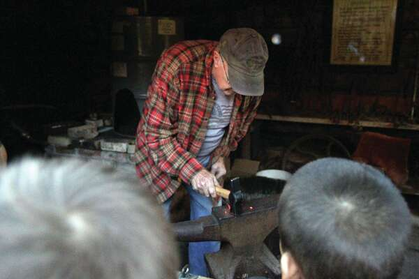 Bad Axe Elementary School second-grade students pay attention to blacksmith Mike Juengling of Saginaw as he explains his technique during a Museum Day at the Pioneer Log Cabin Village in Bad Axe. Students took notes, and even took pictures, as they learned what life was like more than a century ago.