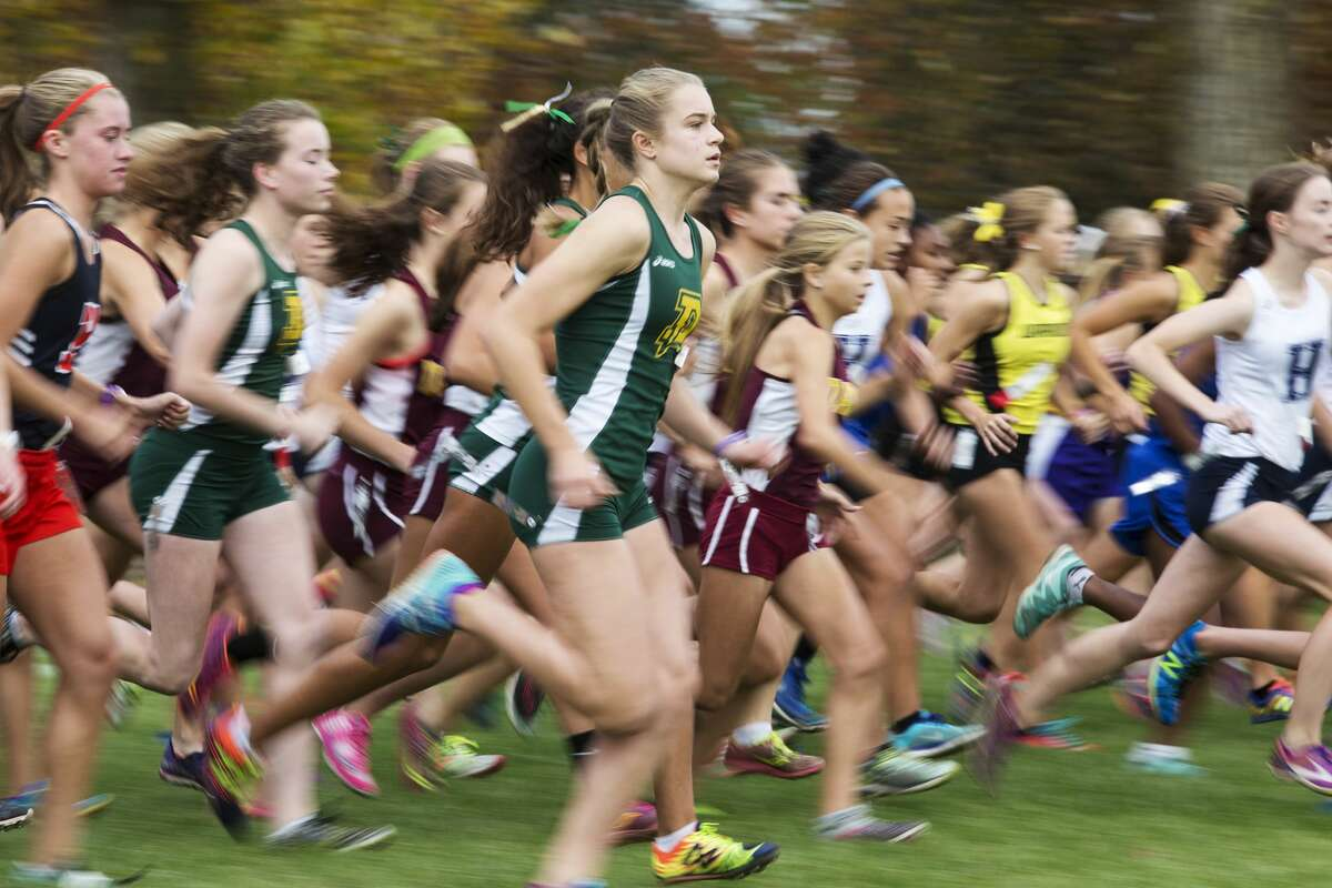 Dow High School runner Anna Jensen runs off the starting line while competing in the Saginaw Valley League cross country championship at Delta College on Wednesday.